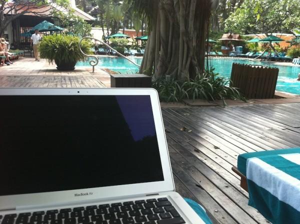 Man schaut von einem Laptop auf einer Liege aus auf einen Pool in tropischer Umgebung