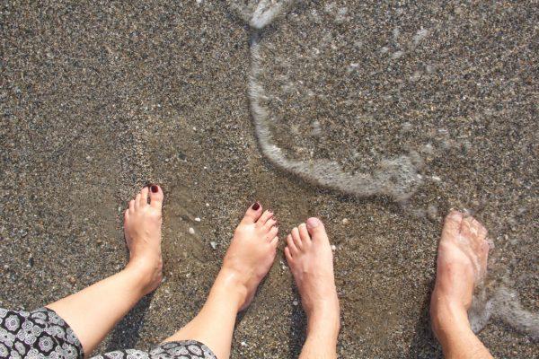 Vier Füße stehen am Strand halb im Wasser
