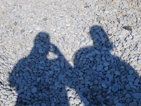 Zwei Schatten auf einer Kiesfläche