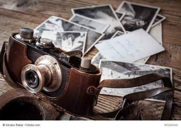 Eine alte Kamera und Fotos als Erinnerungsstücke