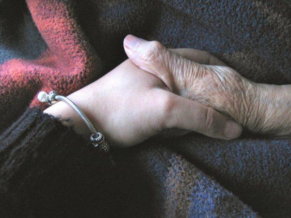 Zwei Hände aus verschiedenen Generationen, die sich umfassen und Zusammenhalt symbolisieren