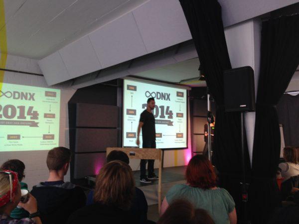 Publikum und eine Bühne mit dem Logo DNX und dem Organisator