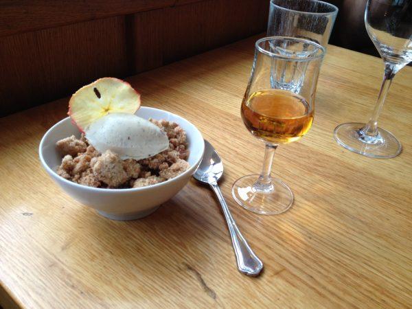 Ein Glas Calvados mit einer Dessertschuessel auf einem hözernen Tisch