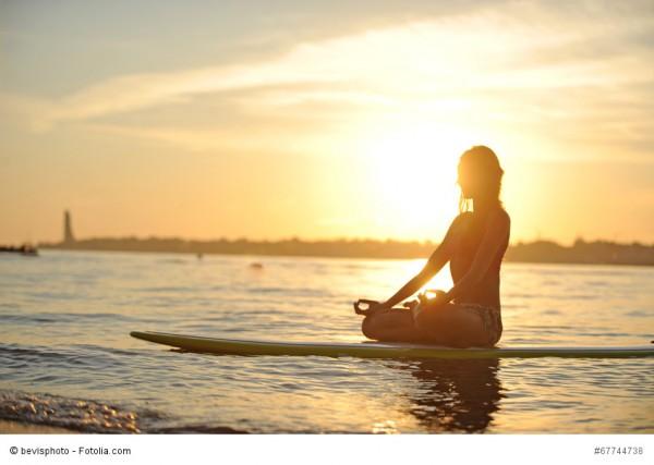 Eine junge Frau sitzt meditierend auf einem Surfbrett an einem Strand mit untergehender Sonne