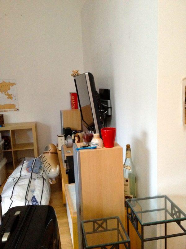 Ein Zimmer mit weißen Wänden, leeren Blumenständern und gepacktem Koffer