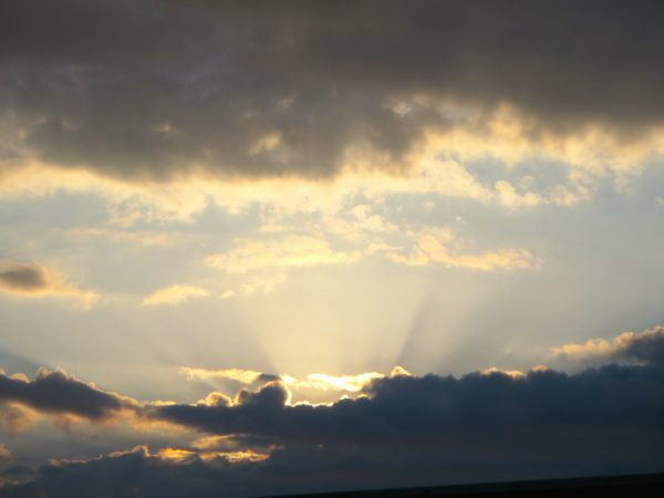 Sonnenstrahlen scheinen hinter dunklen Wolken hervor