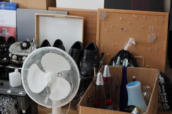 Kram (ein Ventilator, eine Pinnwand, eine Kiste mit Lampen) steht auf dem Boden