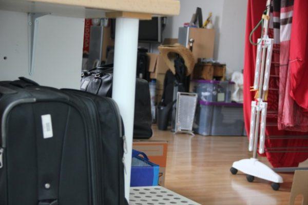 Kisten und Koffer stehen chaotisch in einer Wohnung