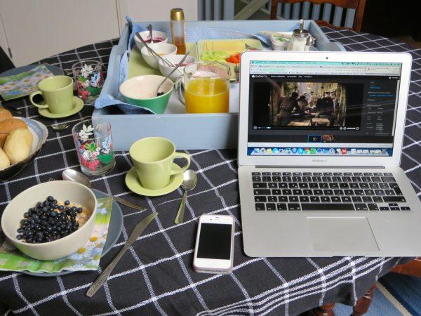 Gedeckter Frühstückstisch mit Laptop und Handy