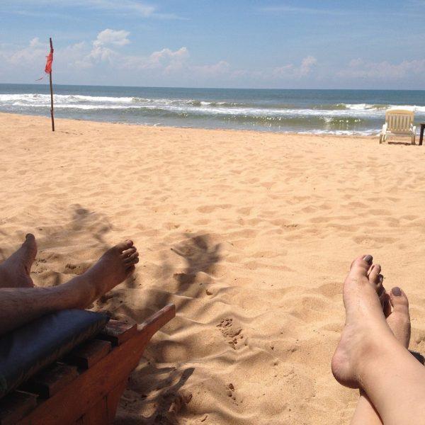 Blick über entspannt auf einer Liege ausgestreckte Beine und Strand zum Meer