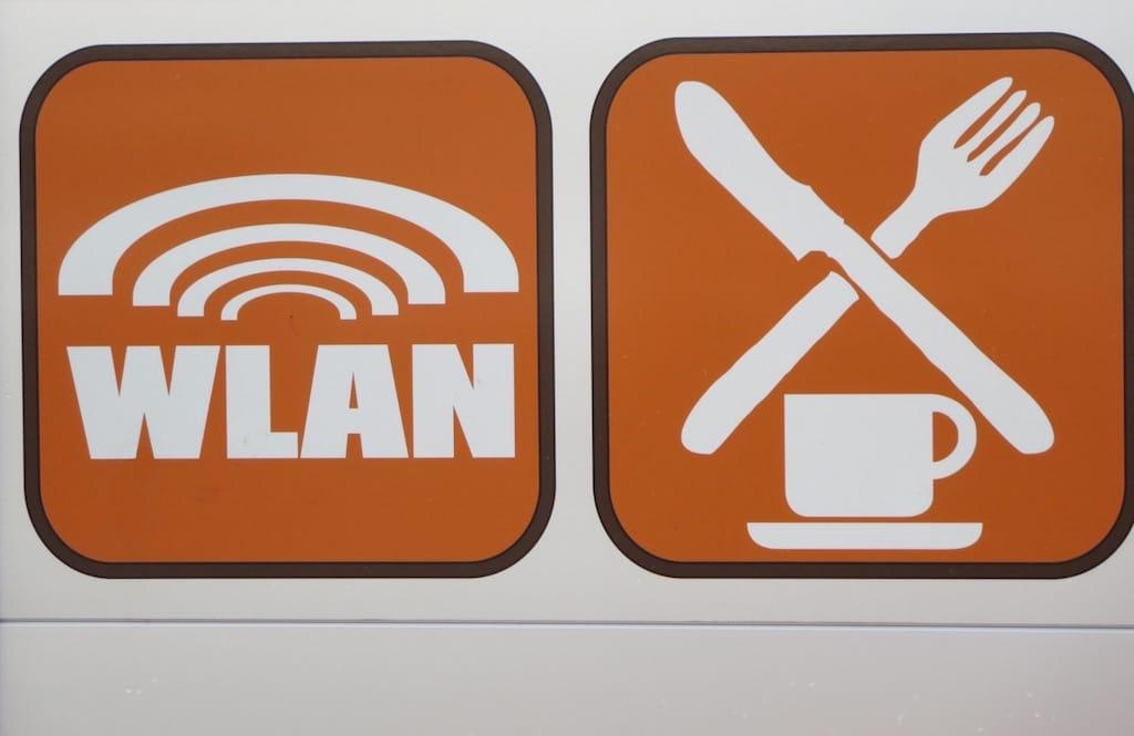 Zwei orange farbene Schilder für WLAN und Essen