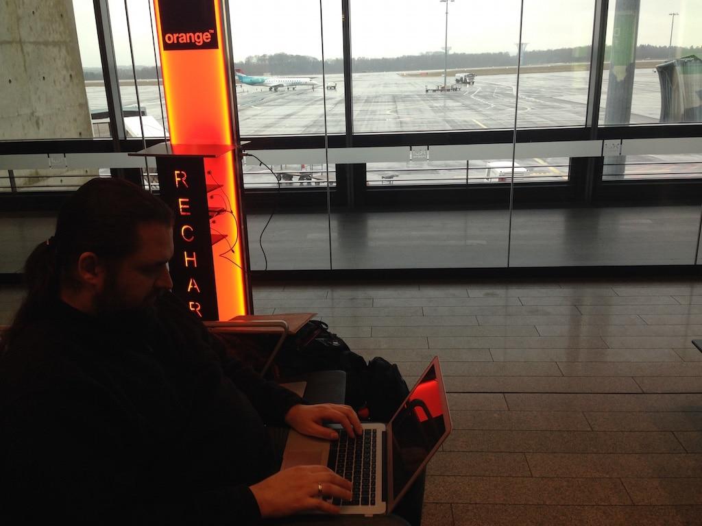 Ein Mann sitzt mit einem Laptop auf einem Flughafen im Hintergrund das Rollfeld