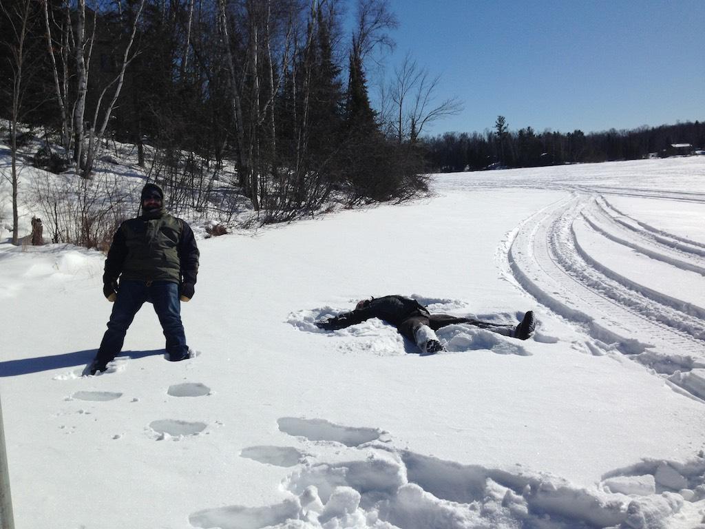 Ein Mensch liegt im Schnee, einer fällt gerade um