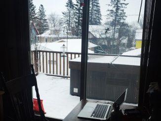 Ein dunkler Raum mit Tisch und aufgeklapptem Laptop und Schneetreiben hinter dem Fenster