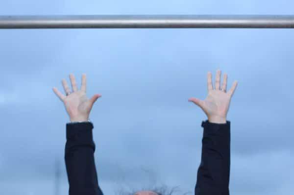 Oben eine Stange und unten Hände, die diese Stange losgelassen haben