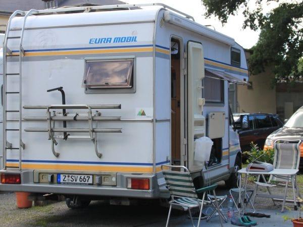 Ein Wohnmobil von eura mobil von hinten auf einem Stellplatz daneben Tisch und Stühle mit einem Laptop