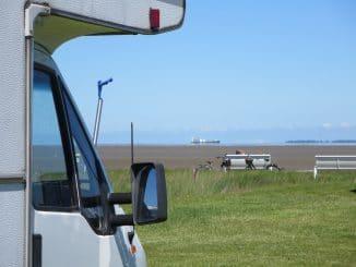 Ein Wohnmobil mit Blick auf eine Bank und dahinter die Nordsee bei Ebbe