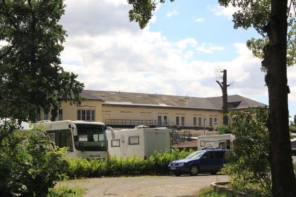 Ein Gebäude davor ein paar Wohnmobile eingebettet in Bäume und Pflanzen