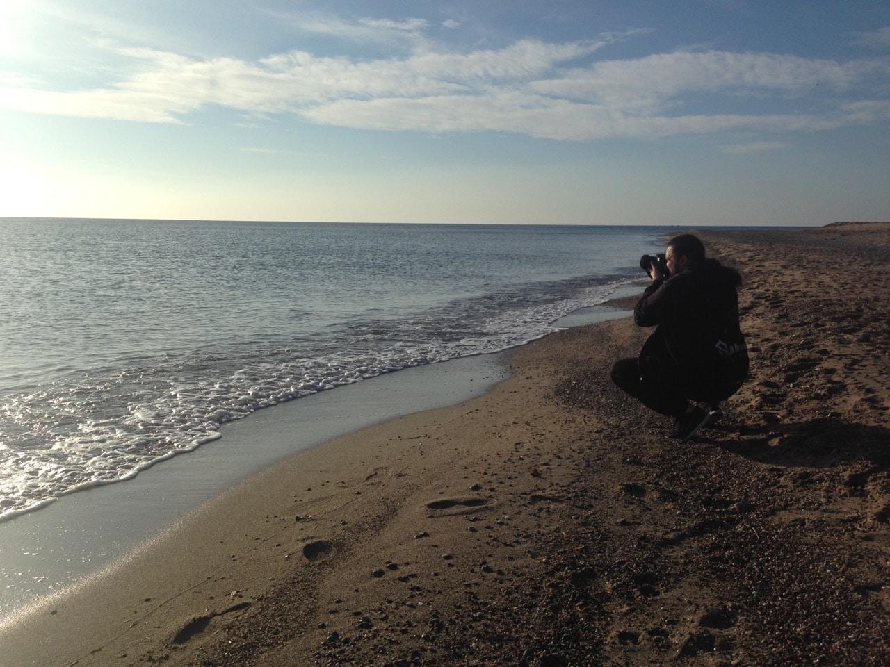 Ein Mann fotografiert hockend das Meer