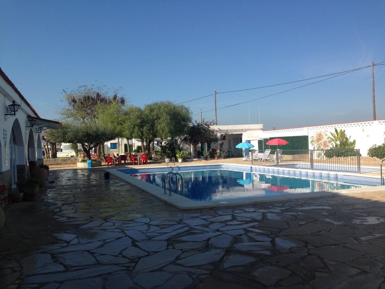 Ein Pool und im Hintergrund ein Spielplatz