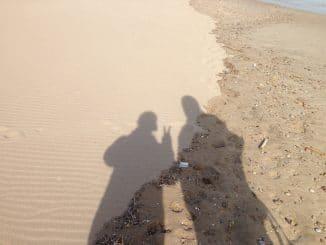 Zwei menschliche Schatten im Sand