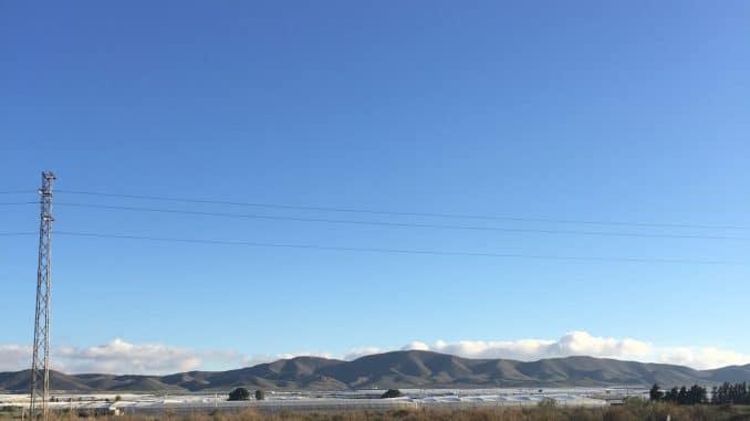 Weiße Gewächshäuser dahinter Berge
