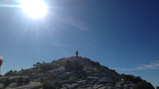 Ein Berggipfel mit einem Mann auf der Spitze mit Sonne