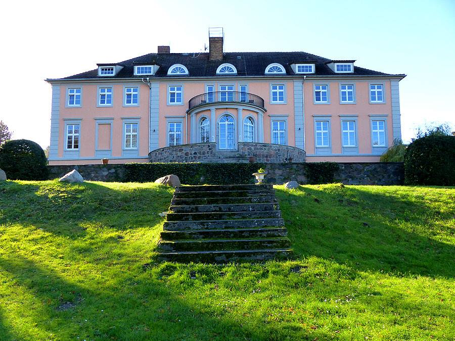 Ein Herrenhaus mit einer Treppe und grüner Wiese davor