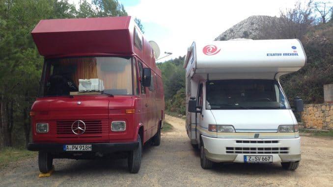 Ein roter Mercedesbus als Wohnmobil und daneben ein weißes EuraMobil