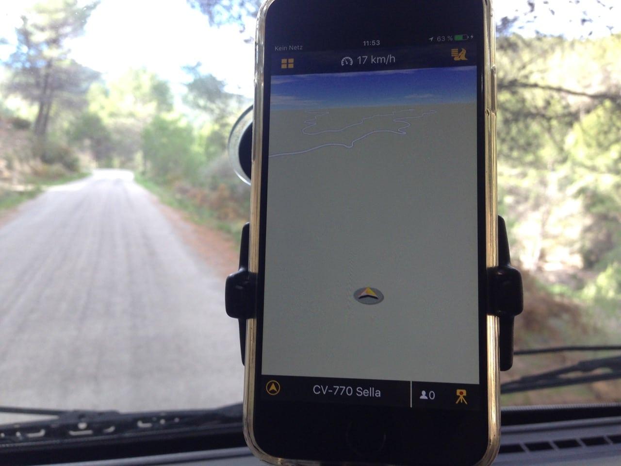 Ein Navigationsgerät mit einem Pfeil im Nirgendwo, im Hintergrund eine Straße