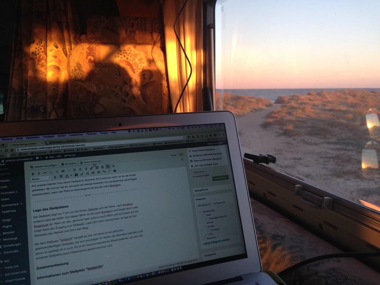 Ein Laptop steht vor einem Fenster, aus dem man das Meer sehen kann