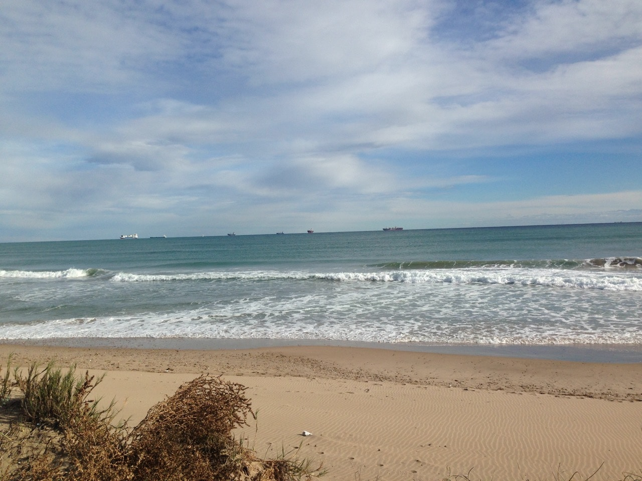 Ein Strand und Wellen unter einem wolkigen Himmel