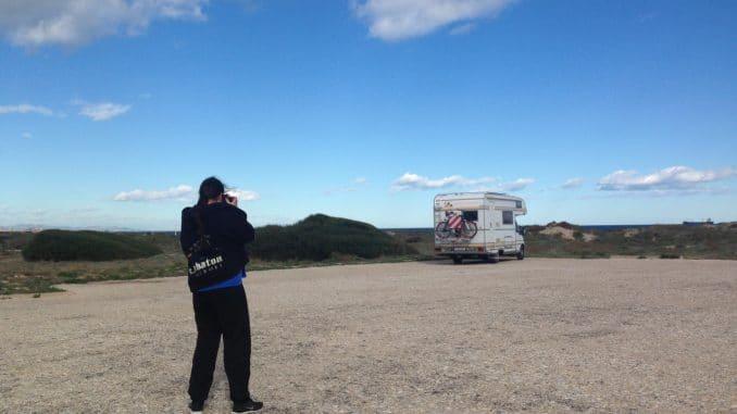 Ein Mann fotografiert ein Wohnmobil, das einsam auf einem Parkplatz am Meer steht