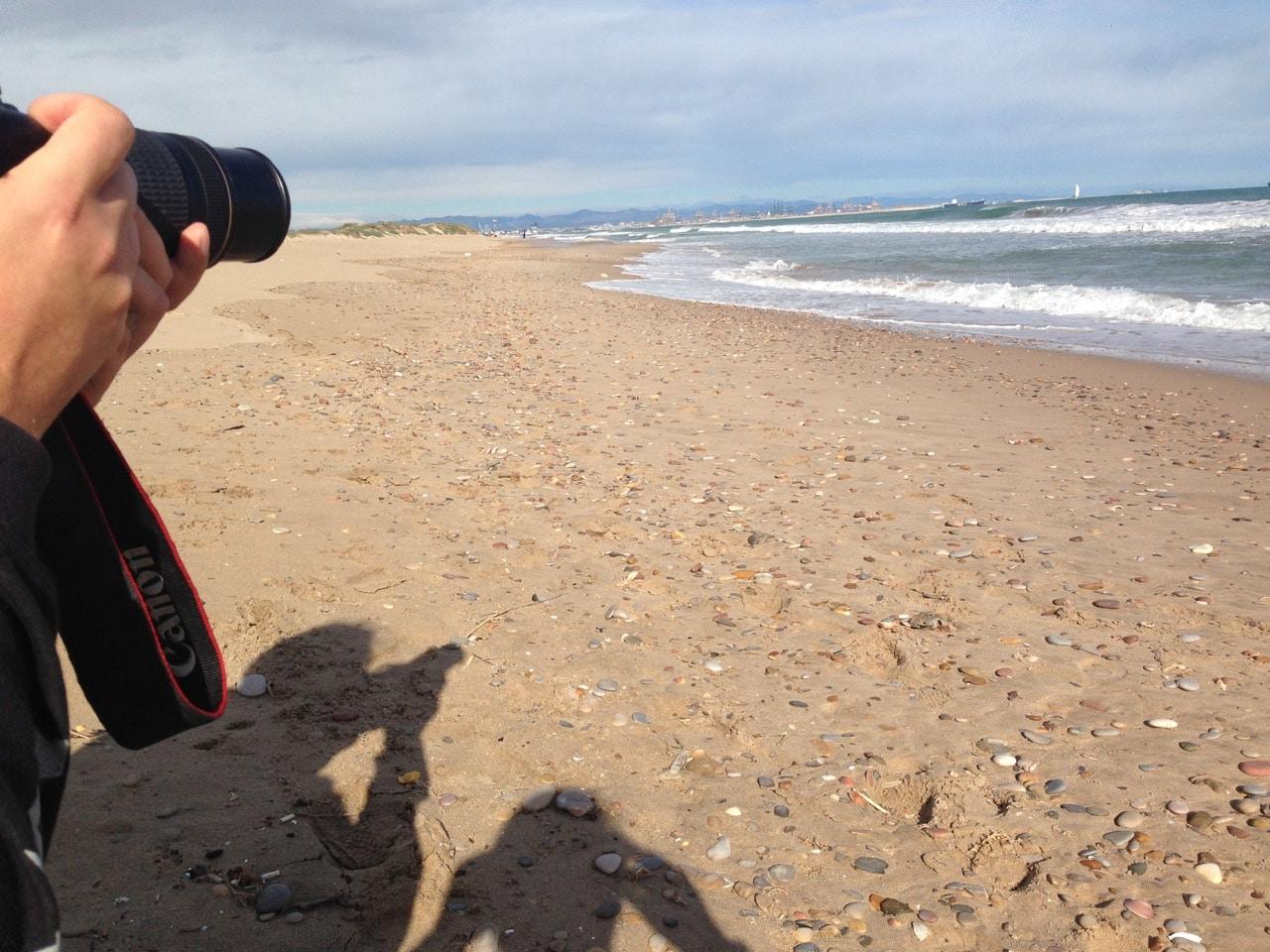 Links im Bild ein Fotoapparat und die Schatten von zwei fotografierenden Menschen, recht Strand und Meer