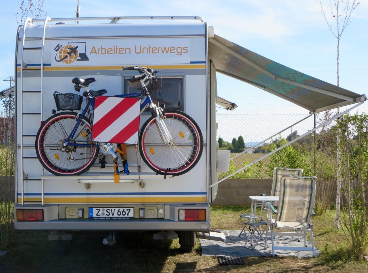 Ein Wohnmobil mit ausgefahrener Markise darunter Stühle