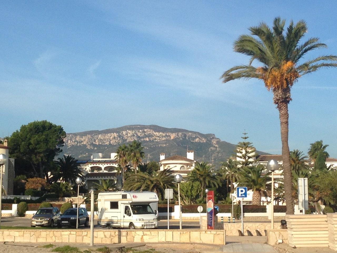 Ein Wohnmobil auf einem Parkplatz im Hintergrund Villen und die Berge