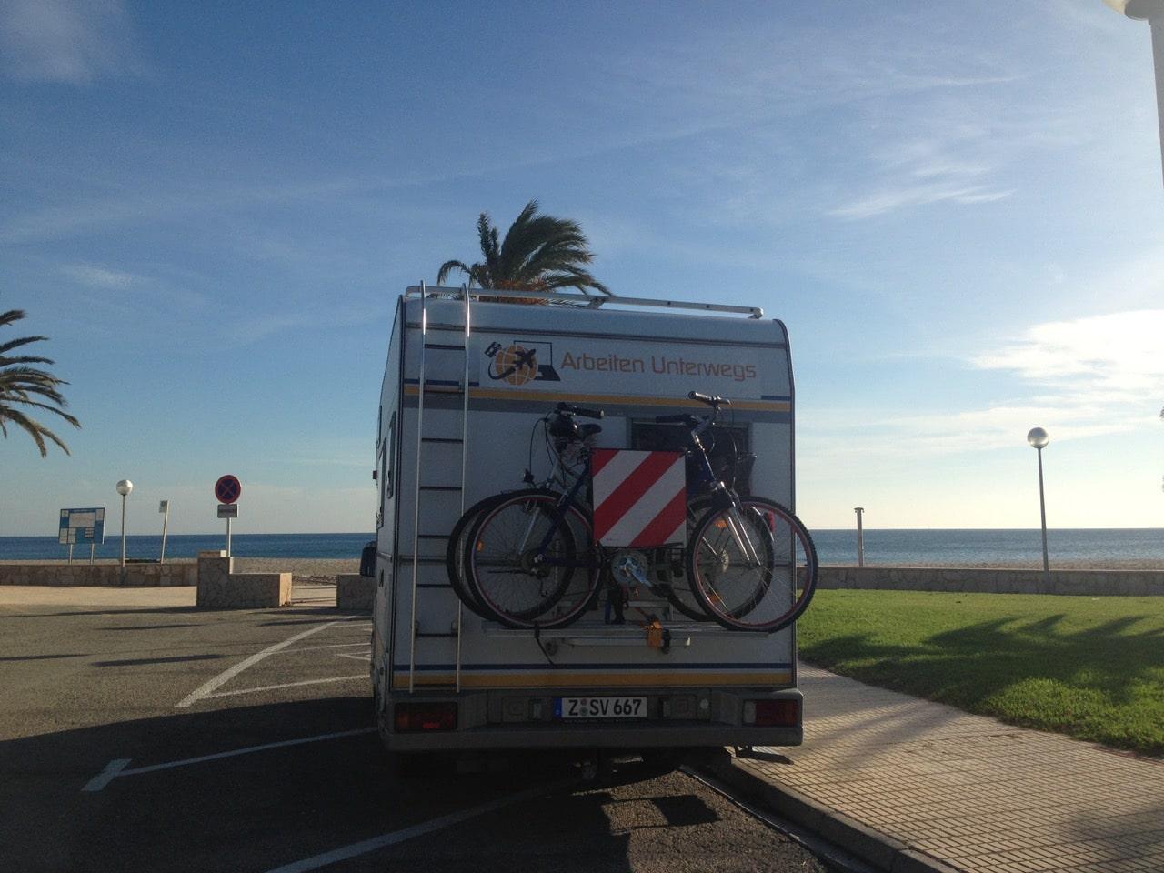 Ein Wohnmobil auf einem Parkplatz und vor dem Wohnmobil das Meer