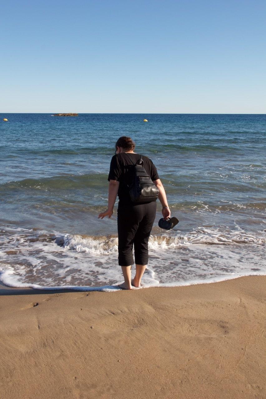 Eine Frau steht zögerlich mit den Füßen im Meer