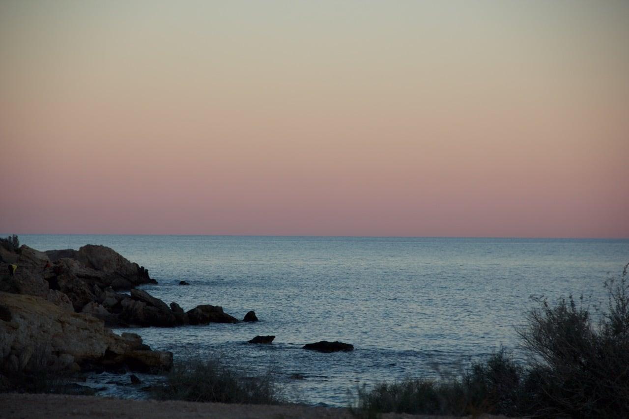 Abendrot an einem Strand mit ein paar Felsen und Gräsern