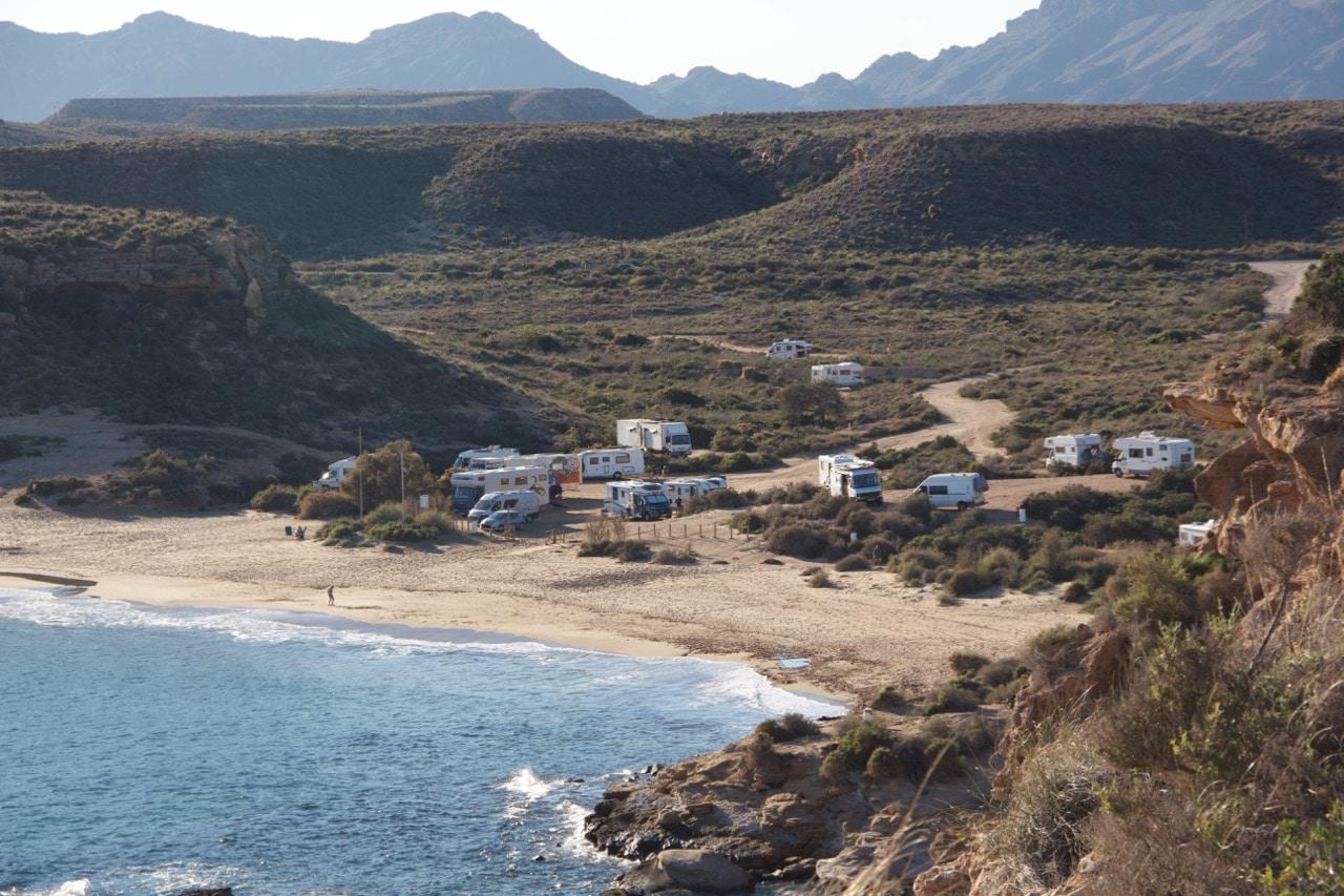 Blick hinunter auf eine Bucht, einen Strand und einige Wohnmobile