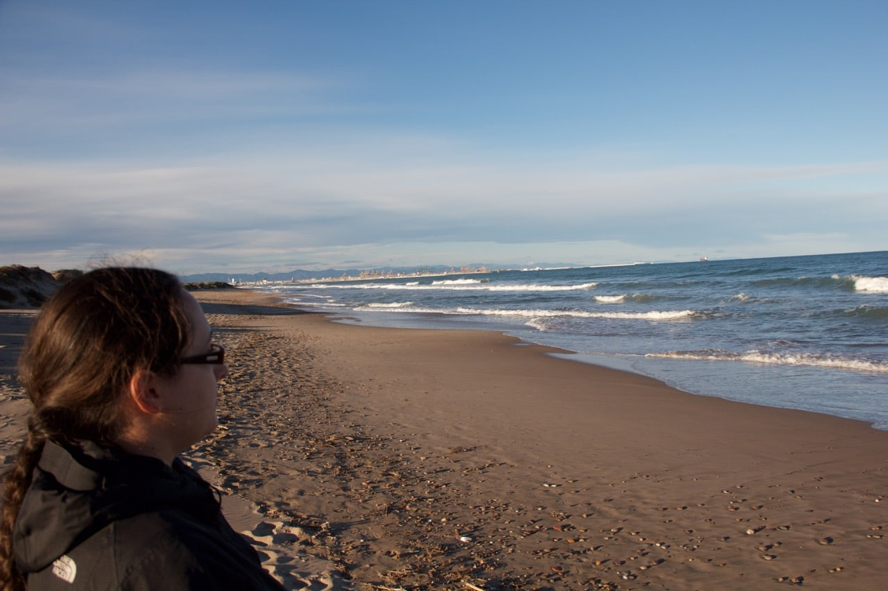 Eine Frau schaut über den Strand auf das Meer