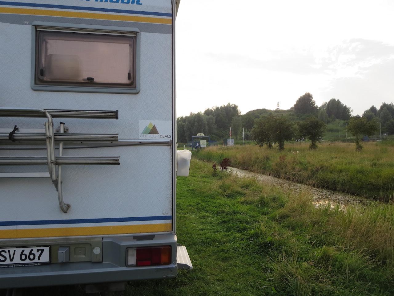 Blick von hinten an einem Wohnmobil vorbei auf ein Flüsschen und eine Wiese