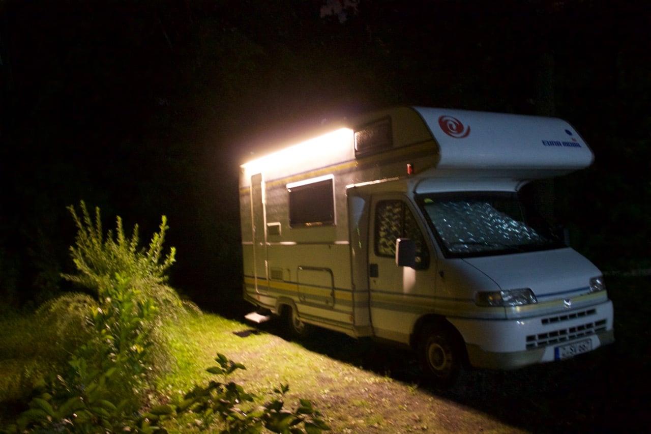 Ein beleuchtetes Wohnmobil bei Nacht