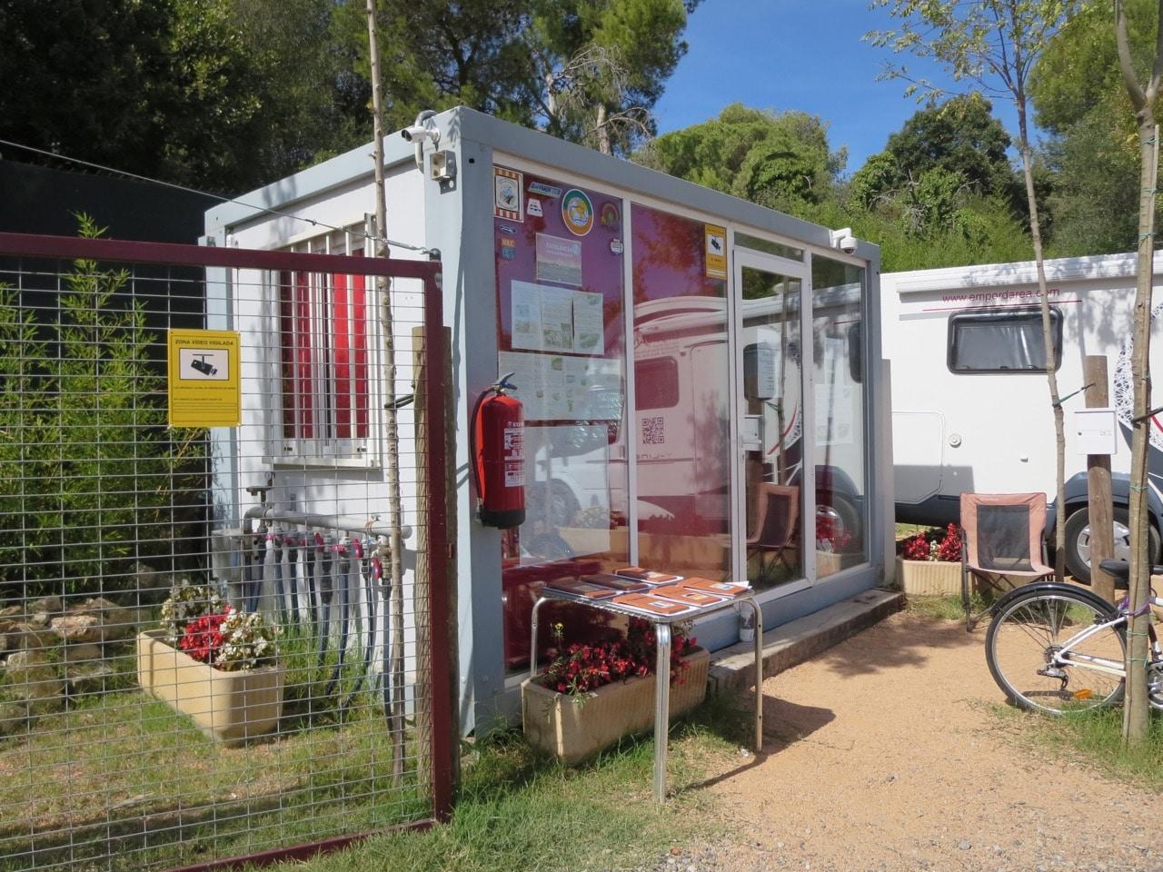 Ein Container neben einem Tor, im Hintergrund ein WOhnmobil