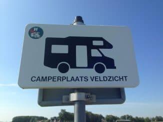 """Ein Schild mit einem Wohnmobil und dem Text """"Camperplaats Veldzicht"""""""