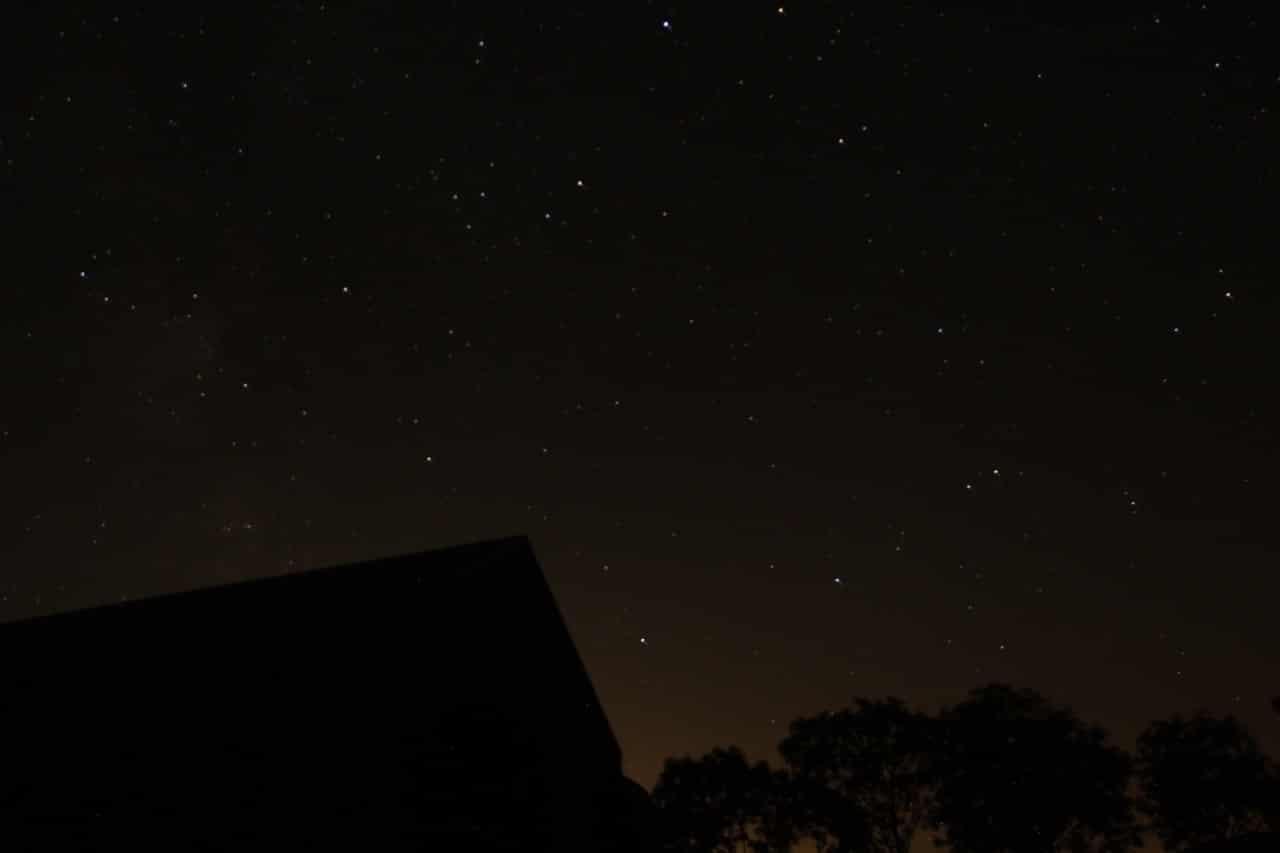 Ein Sternenhimmel und als Schatten ein Haus