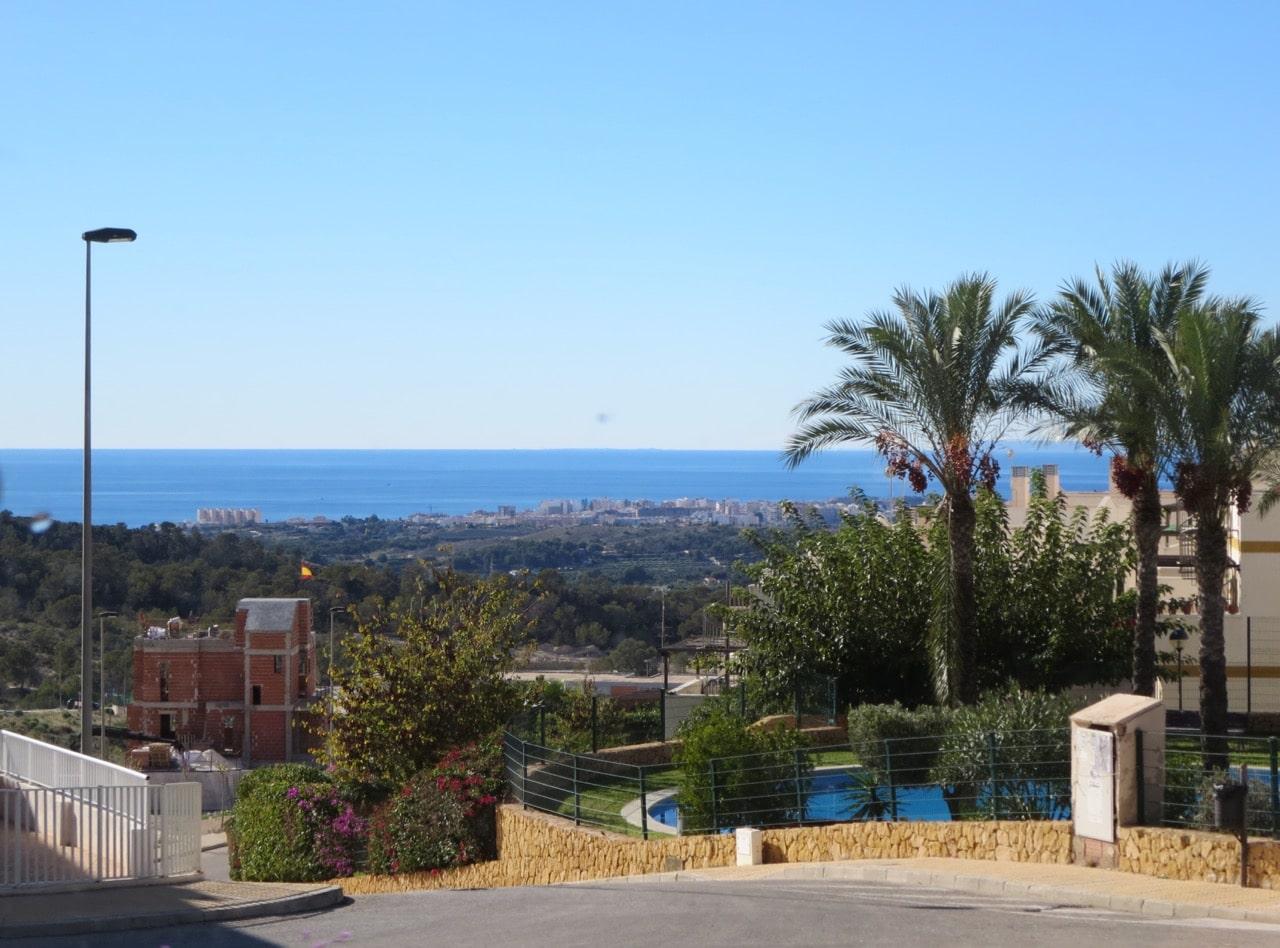 Blick an Häusern vorbei auf das entfernter liegende Meer