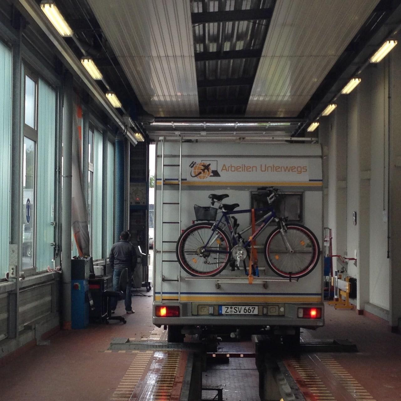 Ein Wohnmobil mit Fahrrädern hinten drauf in einer TÜV-Halle