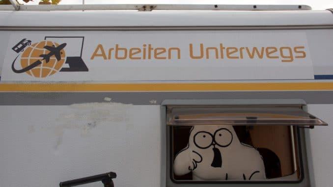 """Ein Wohnmobil von hinten, aus dem Fenster schaut ein Kissen in Katzenform und über dem Fenster ein Aufkleber mit """"Arbeiten unterwegs"""""""