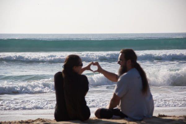 Ein Paar sitzt am Strand, formt mit den Händen ein Herz, im Hintergrund das Meer